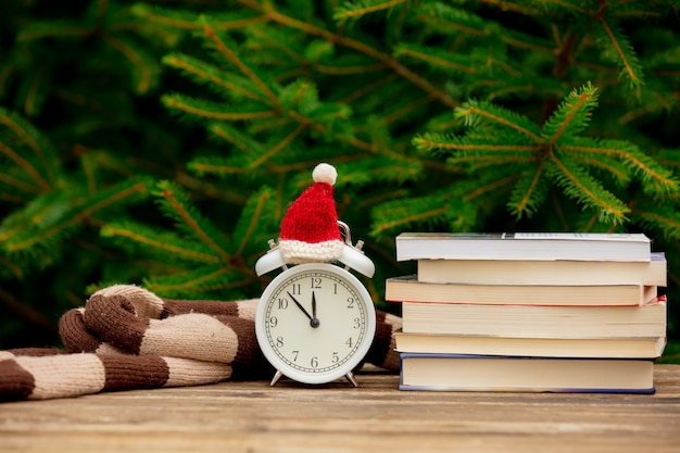 Vintage alarm clock with christmas hat and books on wooden table with spruce branches on background