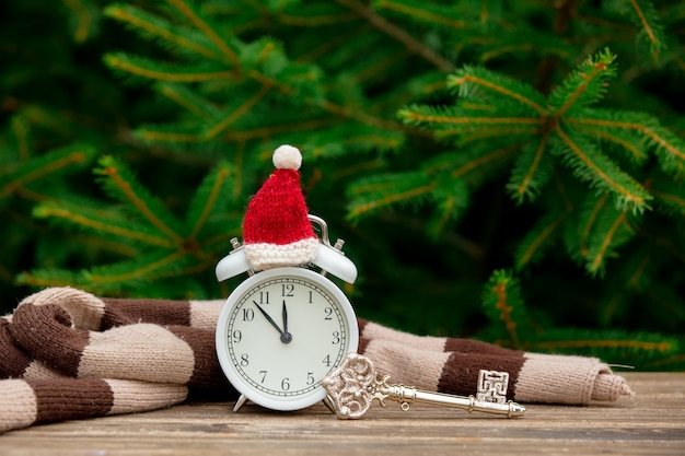 Vintage alarm clock with christmas hat and key on wooden table with spruce branches on background