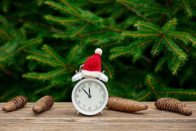 Старинный будильник с рождественской шляпой на деревянном столе с еловыми ветками на фоне