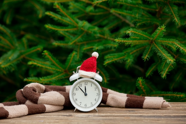 Vintage alarm clock with christmas hat and scarf on wooden table with spruce branches on background