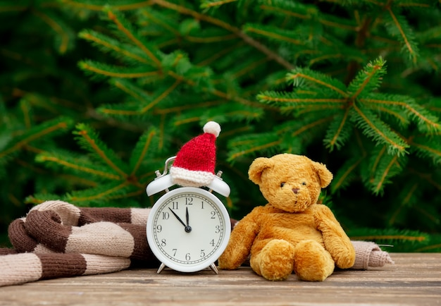 Vintage alarm clock with christmas hat and teddy bear on wooden table with spruce branches on background