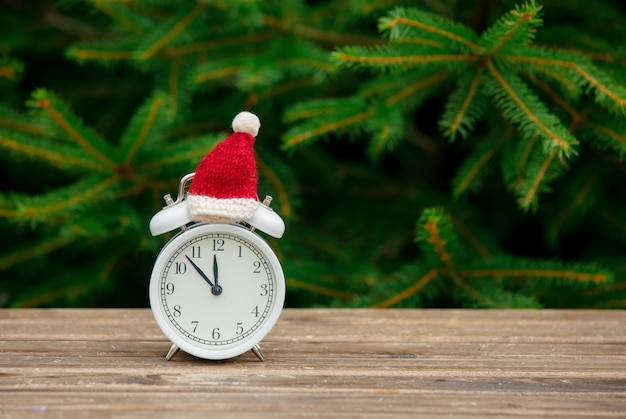 Vintage alarm clock with christmas hat on wooden table with spruce branches on background
