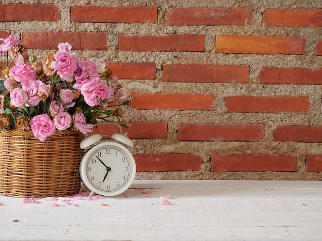 Vintage alarm clock with roses in basket on white wooden table
