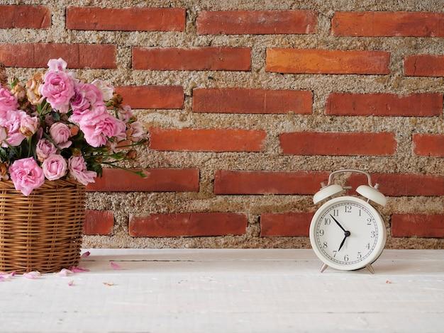 白い木製のテーブルの上のバスケットにバラとヴィンテージ目覚まし時計