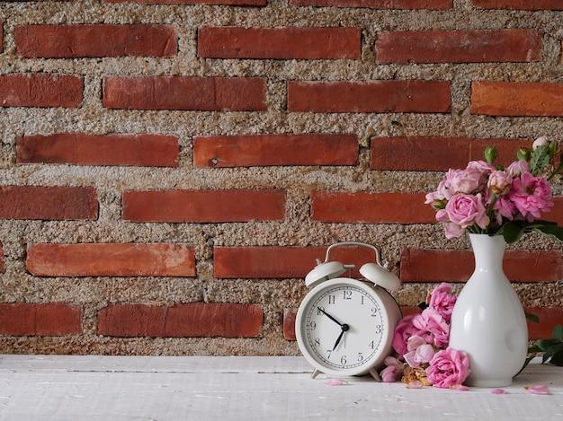 白い木製のテーブルの上に花瓶のバラとヴィンテージ目覚まし時計