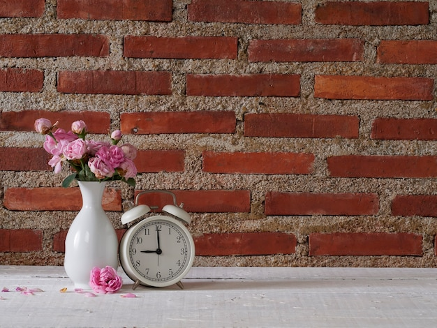 Vintage alarm clock with roses in vase on white wooden table