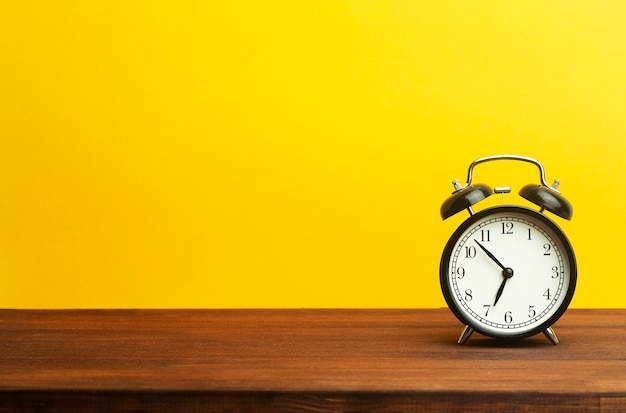 Vintage alarm clock on a yellow background. black alarm clock showing morning time on the table. time concept.