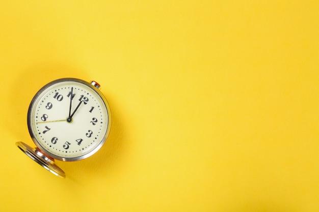 Vintage alarm clock on yellow