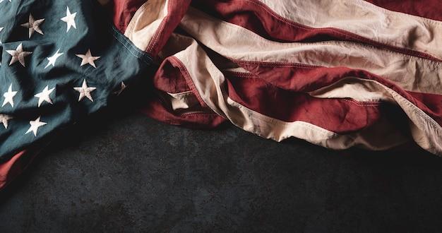 Vintage american flags against dark stone background