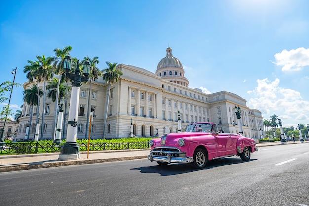 Винтажный американский ретро автомобиль carconvertible едет по асфальтовой дороге перед капитолием в старом городе гаваны. туристическое такси кабриолет.
