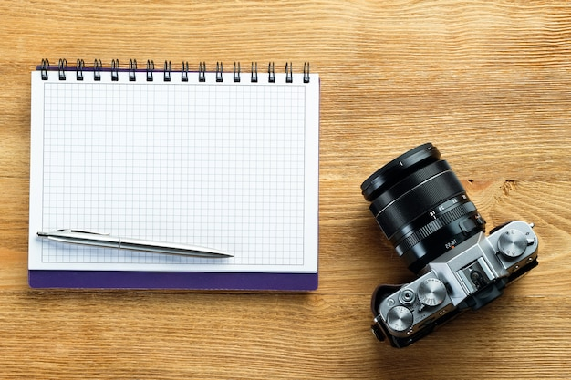 Vintage analog camera, pen and notepad for notes on a wooden table. photographer's items in the workplace. preparing for shooting.