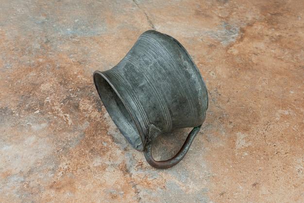 Vintage antique ancient kettle on marble background