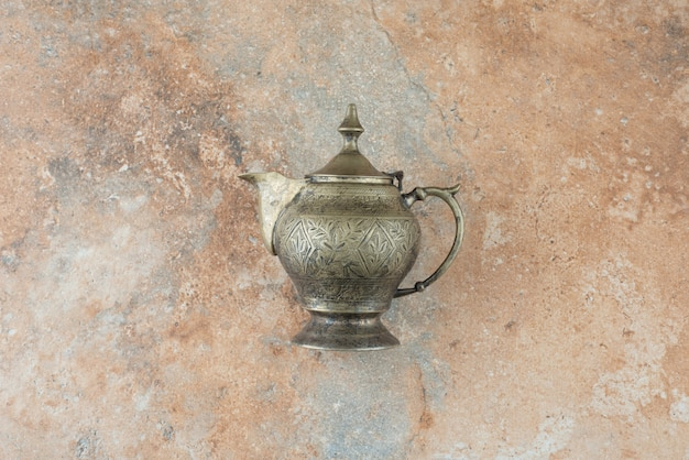 Vintage antique ancient kettle on marble background