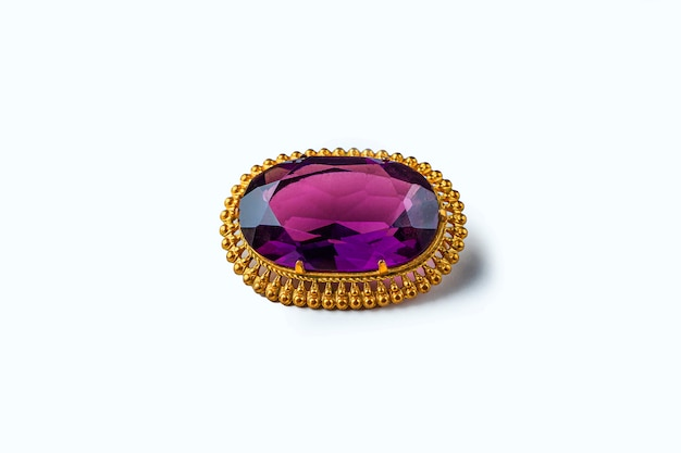 Vintage antique brooch with a large semi-precious purple stone on white