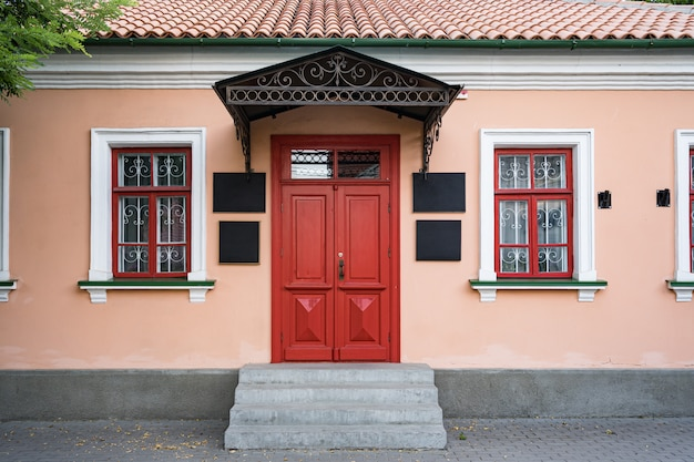 Vintage architecture classical facade building with red door