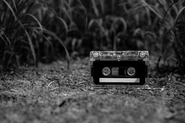 庭の床にヴィンテージのオーディオカセットテープ。 - モノクロ