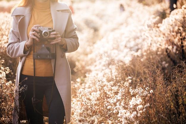 ヴィンテージ秋。ヴィンテージカメラを持つ少女は、日没時にふわふわのタンポポのフィールドを歩きます