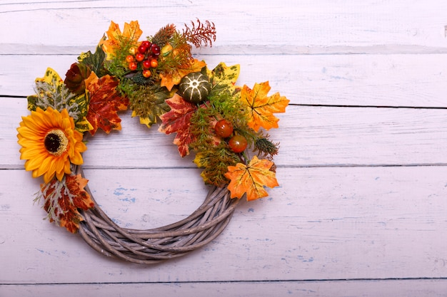 Vintage autumn wreath from leaves and flowers on shabbi wooden backgorund with copy