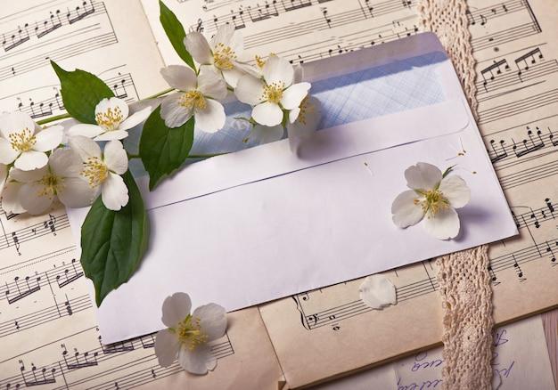Vintage background - old letters, notes jasmine branch and blank envelope