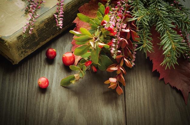 古い本、森の花とベリーとヴィンテージの背景。ノスタルジックなレトロなクリスマス作曲。