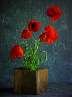 Vintage background with red poppies in a wooden vase