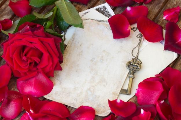 赤いバラの花びらとアンティークゴールドキーとヴィンテージの背景