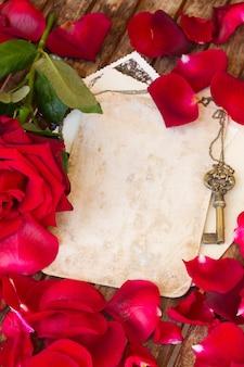 赤いバラの花びらと金の鍵とヴィンテージの背景