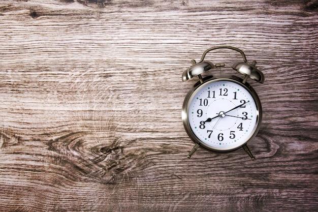 木製のテーブルにレトロな目覚まし時計とビンテージ背景