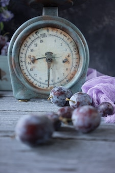 Vintage balance and fresh plums on wooden table