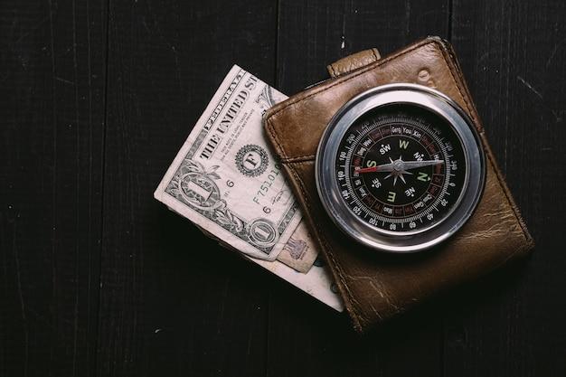 Старинные банкноты на деревянной доске со старым старинным компасом