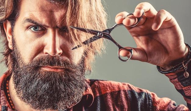 Винтажная парикмахерская, бритье. мужчина в парикмахерской, стрижка, бритье. бородатый мужчина, изолированные на сером фоне. мужская стрижка в парикмахерской.