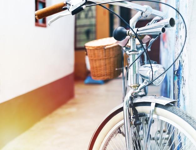 ヴィンテージ自転車駐車場は、家の壁に傾いています。夏のヴィンテージコンセ