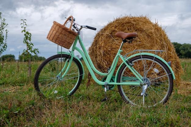 わらのスタックの背景に木製のバスケットとヴィンテージ自転車