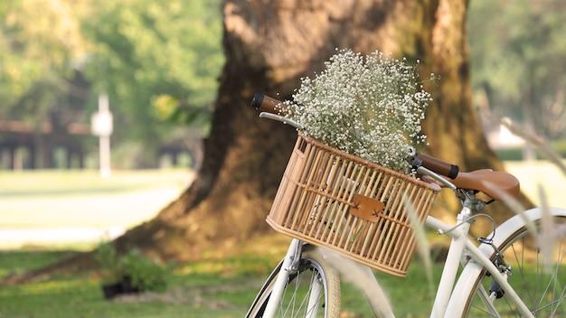 Винтажный велосипед или велосипед и деревянная корзина коричневого цвета спереди и маленькие белые цветы