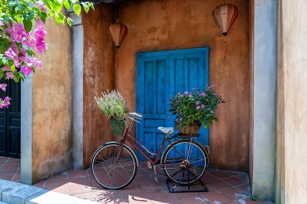 ダナンの古い建物の横に花がいっぱい入ったかご付きビンテージバイク