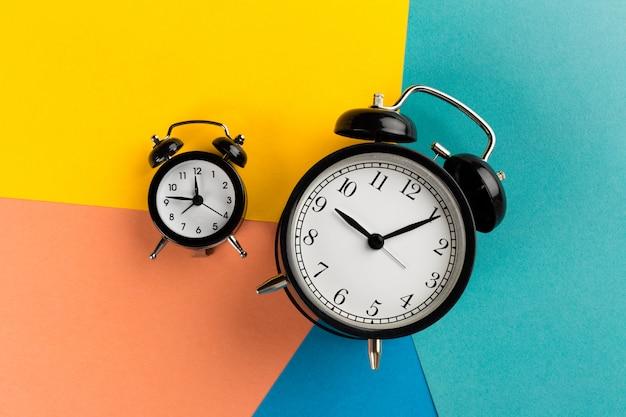 Vintage black alarm clock on colorful paper