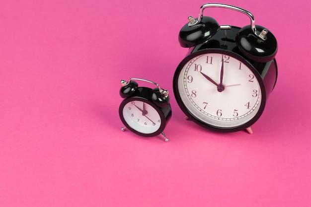 Vintage black alarm clock on lilac