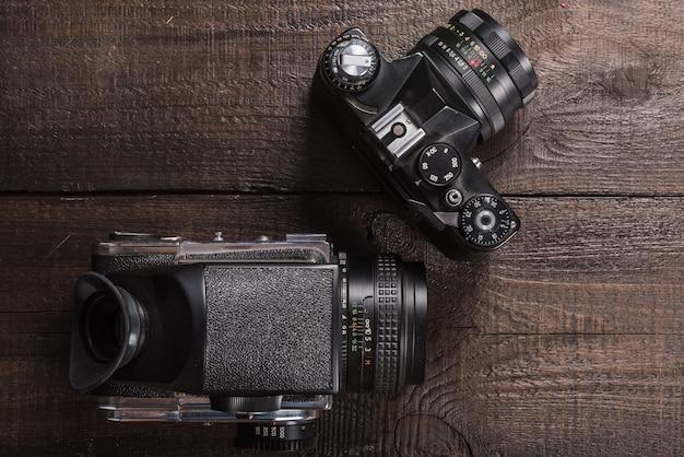 렌즈와 천연 나무의 갈색 배경에 빈티지 블랙 필름 카메라
