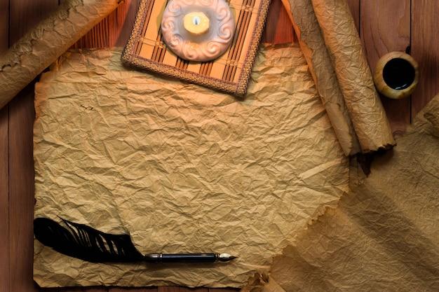 ヴィンテージの黒い羽ペンと古い空白の紙の上のキャンドル