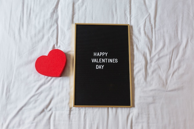 Vintage blackboard with happy valentines day message and a red heart over with background. home, indoors. concept