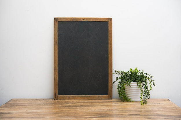Vintage blackboard with wooden frame with a pot of plants