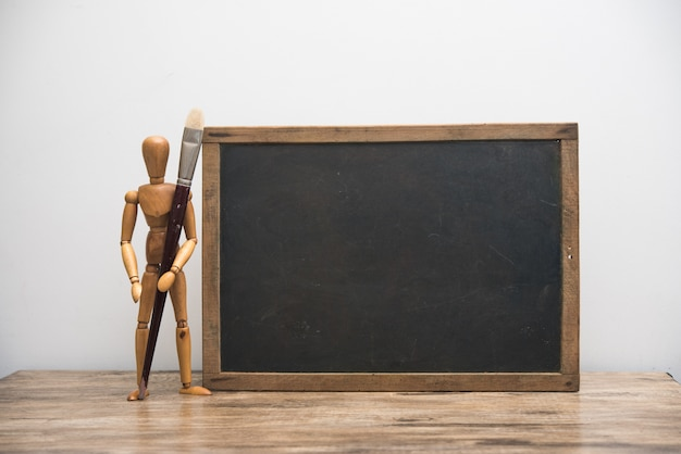 Vintage blackboard with wooden frame with wooden doll