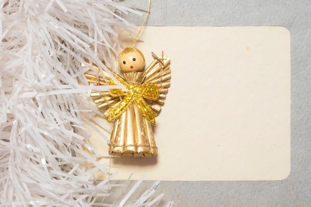 Винтажная пустая картонная рамка с игрушечной фигуркой ангелочка и белой мишурой