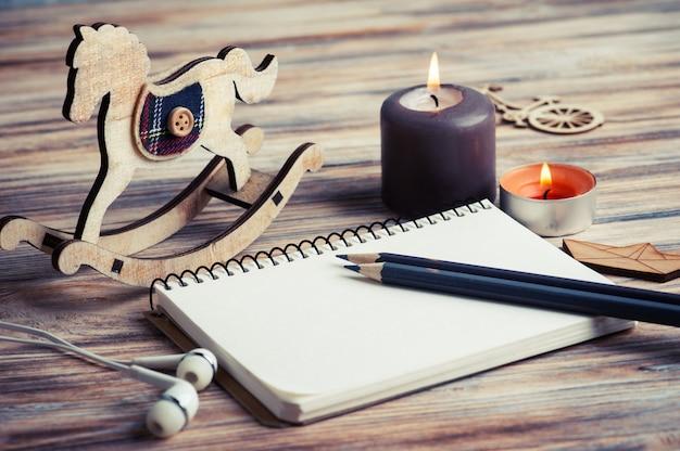 Винтажная пустая записная книжка, ароматические свечи, деревянная лошадка-качалка и игрушки в деревенском стиле
