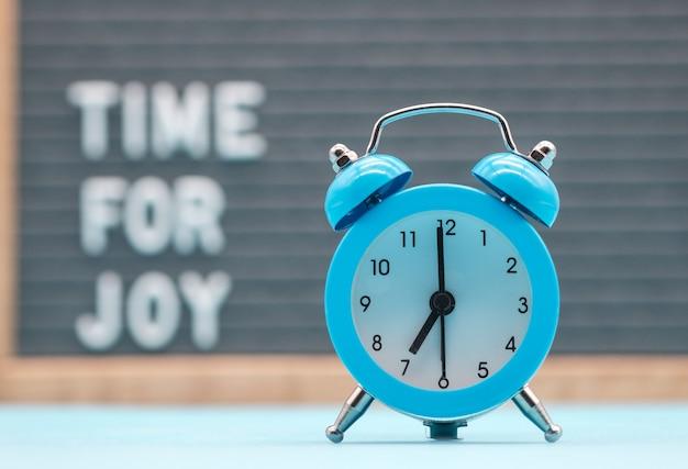 碑文の背景にあるヴィンテージの青い目覚まし時計英語で喜びの時間