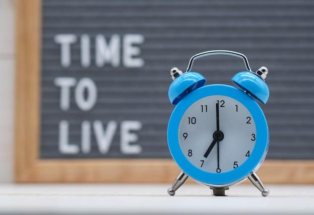 生きるために英語の時間のテキスト上のヴィンテージの青い目覚まし時計