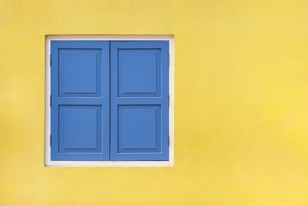 コピースペースとクリッピングパスで黄色に分離されたヴィンテージの青いシャッターと木製の窓