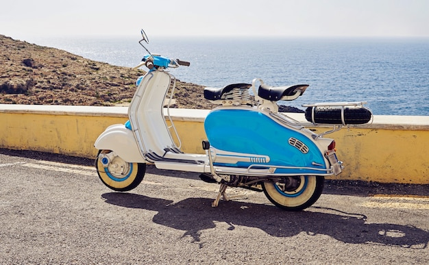 Vintage blue-white two-seater scooter parked on street