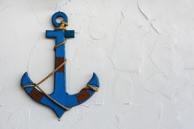 A vintage blue wood anchor on white plaster cement texture wall background, copy space