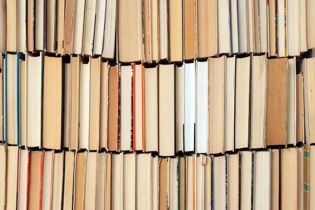 ヴィンテージ本の背景。古くて使用済みのハードカバーの本が隣り合って積み上げられています。教育と勉強の概念。誰でもない